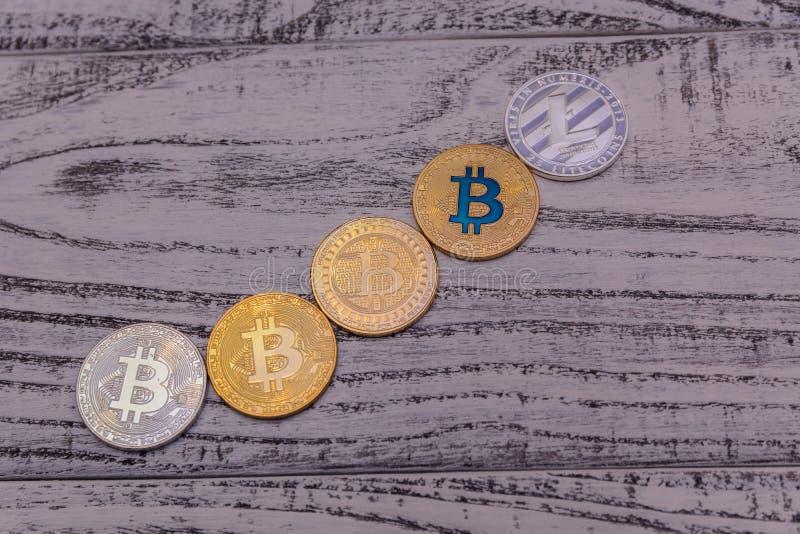 Bitcoins e o litecoin de prata encontram-se no close up de madeira velho da tabela imagens de stock royalty free
