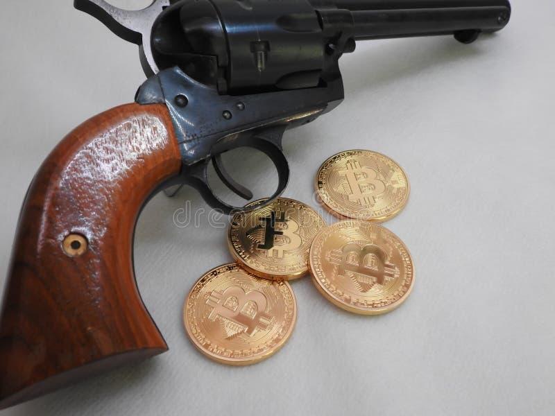 Bitcoins e revólver fotos de stock