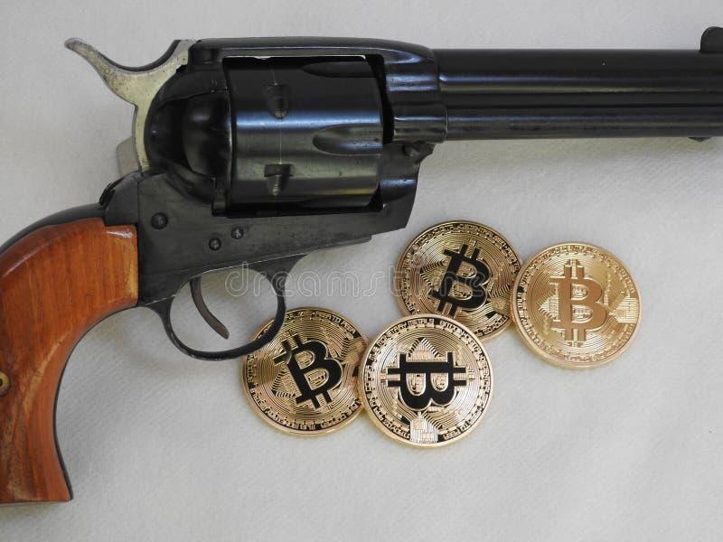 Bitcoins e revólver imagem de stock
