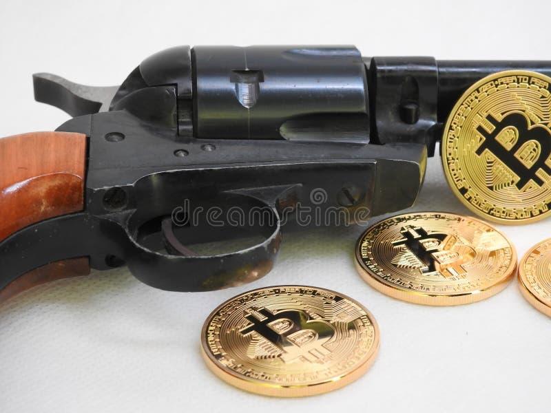 Bitcoins e revólver fotos de stock royalty free