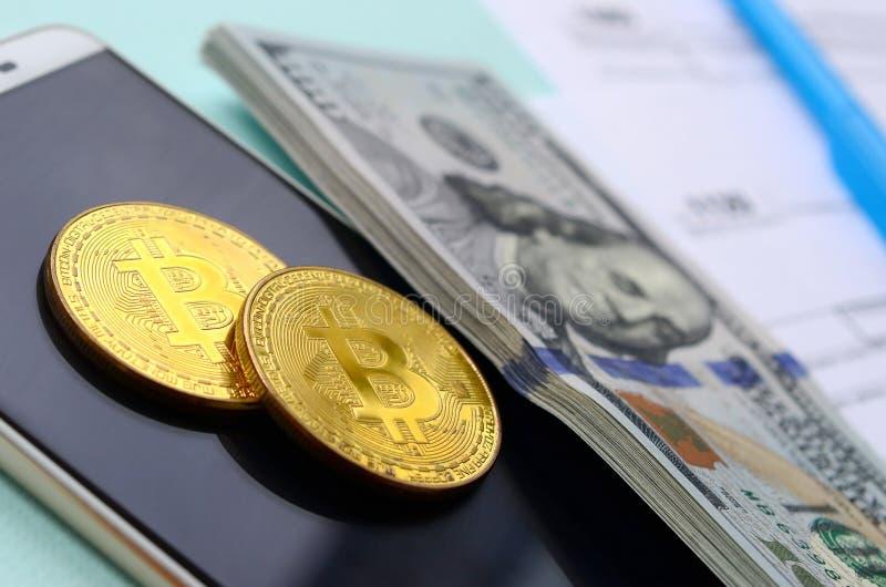 Bitcoins encontra-se com os formulários de imposto, cem notas de dólar e smartphone em um claro - fundo azul Declaração de rendim imagem de stock royalty free