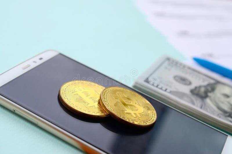 Bitcoins encontra-se com os formulários de imposto, cem notas de dólar e smartphone em um claro - fundo azul Declaração de rendim fotografia de stock