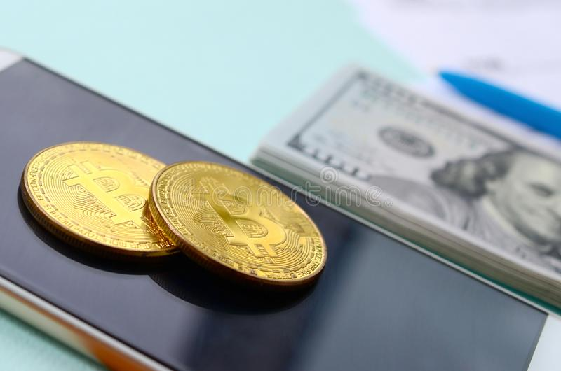 Bitcoins encontra-se com os formulários de imposto, cem notas de dólar e smartphone em um claro - fundo azul Declaração de rendim fotografia de stock royalty free