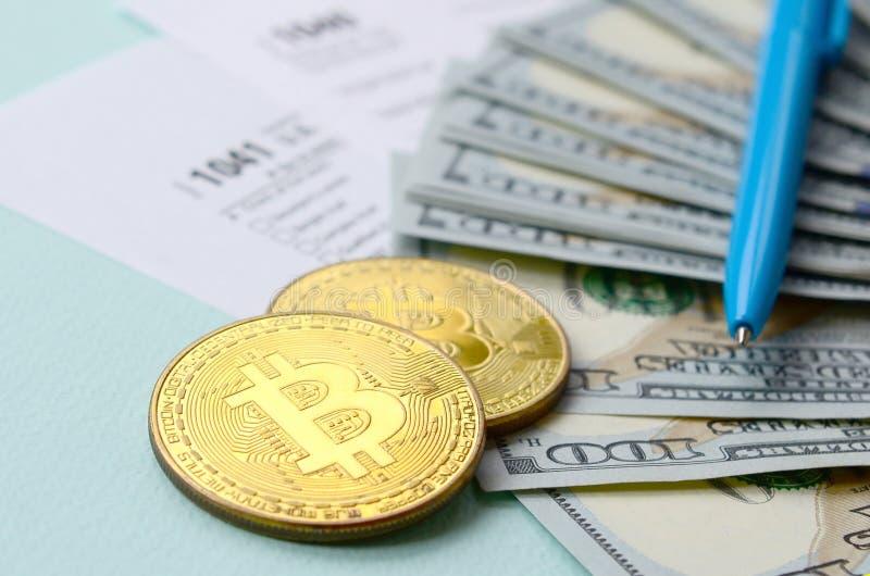 Bitcoins encontra-se com os formulários de imposto e cem notas de dólar em um claro - fundo azul Declaração de rendimentos da ren imagens de stock