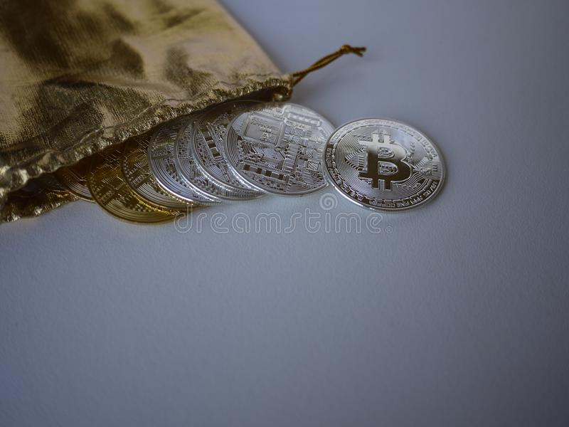 Bitcoins are flow out from a golden sack. stock images