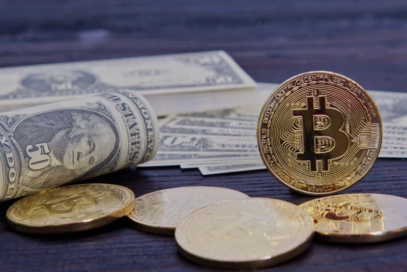 Bitcoins i dolarowi banknoty na stole zdjęcia stock