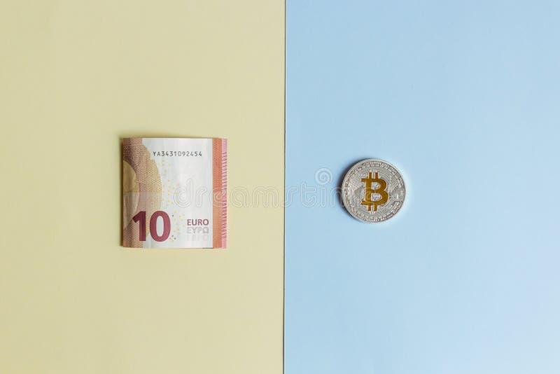 Bitcoins i euro na pastelowym tle pojęcie wybór między cryptocurrency i papierowym pieniądze obraz stock