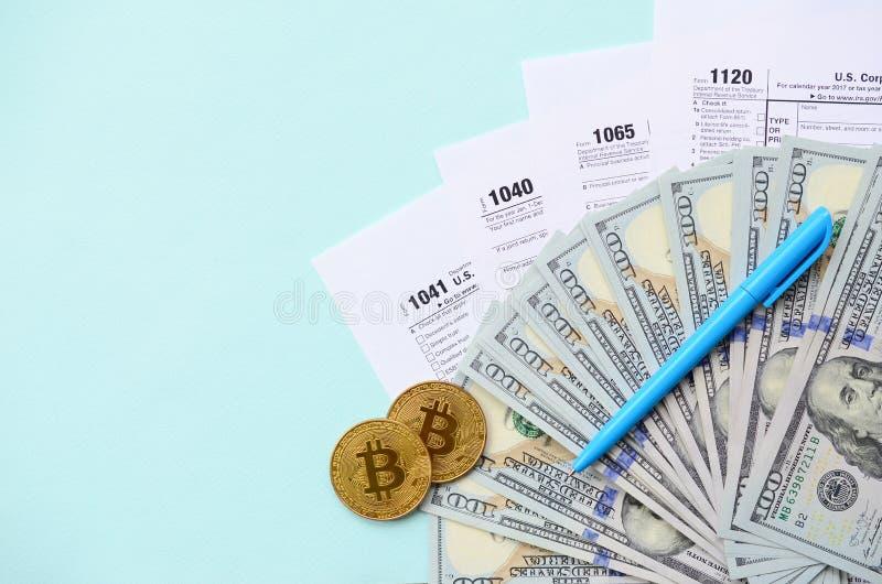 Bitcoins liegt mit den Steuerformularen und hundert Dollarscheinen auf einem hellblauen Hintergrund Einkommenssteuererklärung stockfotografie