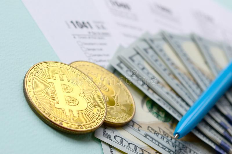 Bitcoins lies with the tax forms and hundred dollar bills on a light blue background. Income tax return royalty free stock photo