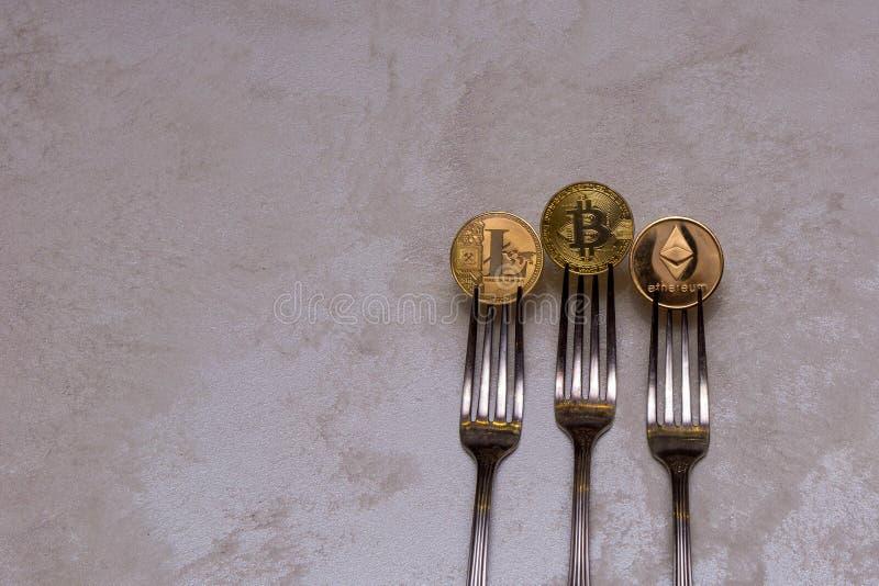 Bitcoins, litecoin en ethereum in drie zilveren vorken stock afbeelding