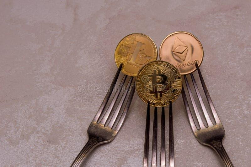 Bitcoins, litecoin en ethereum in drie zilveren vorken stock afbeeldingen