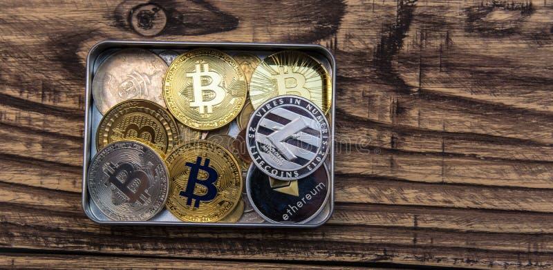 Bitcoins, litecoin en ethereum liggen in metaaldoos op oude houten achtergrond stock foto's