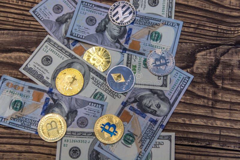 Bitcoins, litecoin en ethereum liggen op één hubred dollarrekeningen op oude houten achtergrond royalty-vrije stock afbeelding