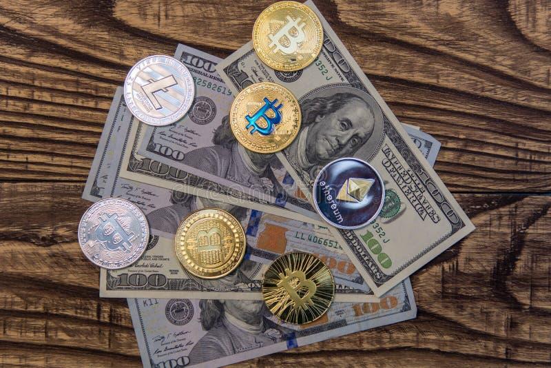 Bitcoins, litecoin en ethereum liggen op één hubred dollarrekeningen op oude houten achtergrond stock foto