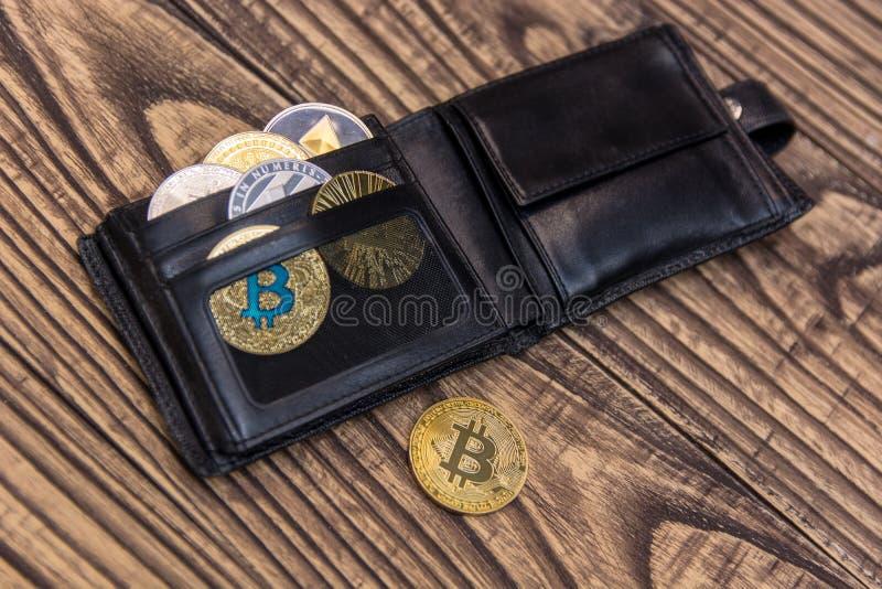 Bitcoins, litecoin en ethereum in zwarte leerportefeuille op houten achtergrond stock fotografie