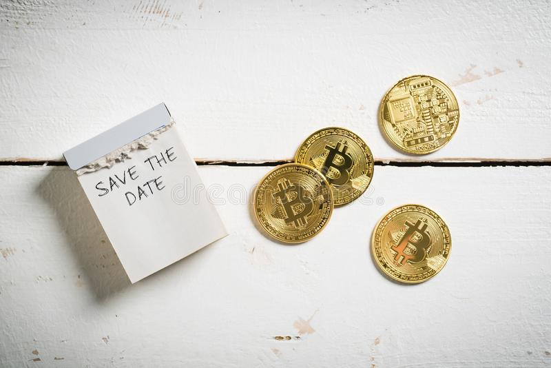 Bitcoins met afscheuringskalender en het bericht 'sparen de datum ' stock afbeeldingen