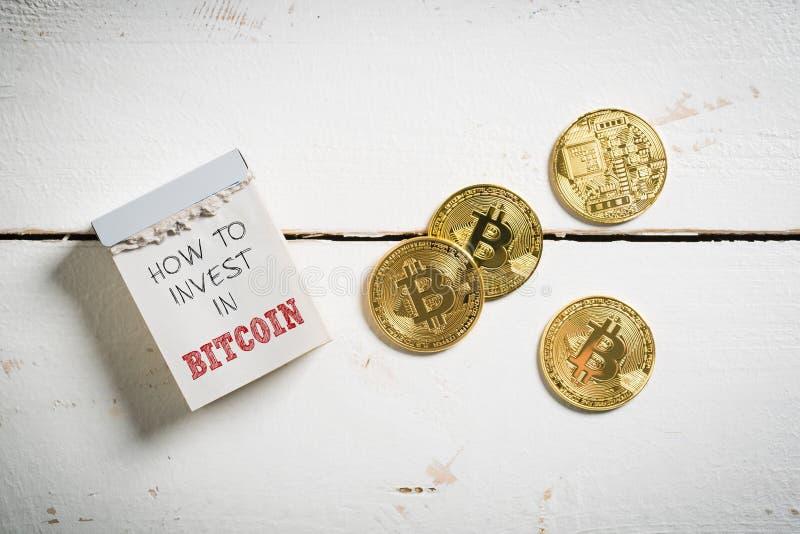 Bitcoins met afscheuringskalender en het bericht ` hoe te in Bitcoin ` te investeren royalty-vrije stock afbeeldingen