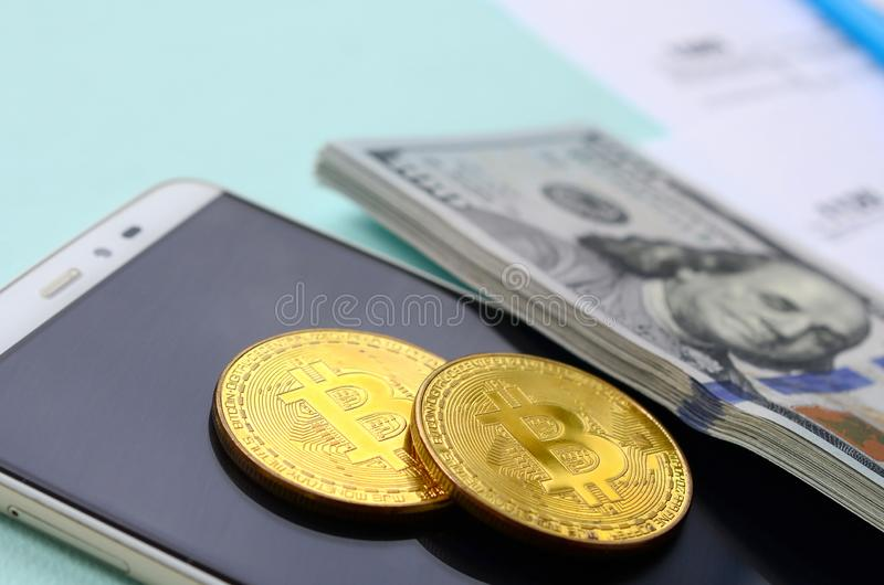 Bitcoins miente con las formas de impuesto, cientos billetes de dólar y smartphone en un fondo azul claro Declaración sobre la re foto de archivo libre de regalías