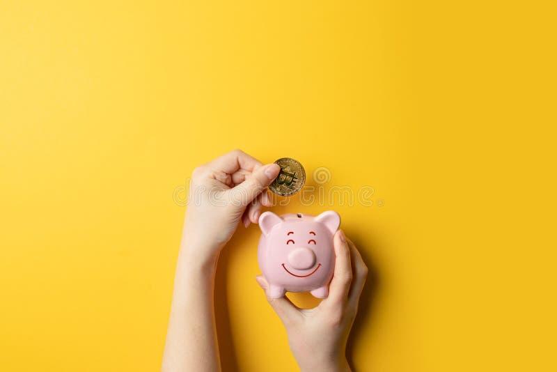 Bitcoins, moneda y hucha en fondo amarillo fotos de archivo libres de regalías