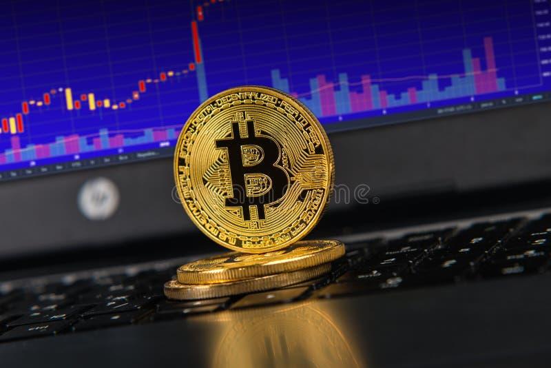 Bitcoins na laptop klawiaturze, wykres na ekranie zdjęcia royalty free