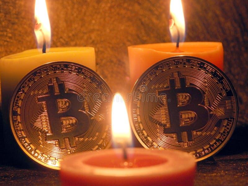 Bitcoins que se inclina en velas foto de archivo libre de regalías