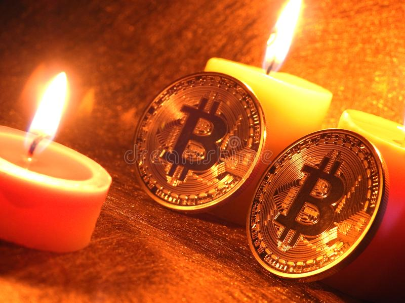 Bitcoins que se inclina en velas fotografía de archivo libre de regalías