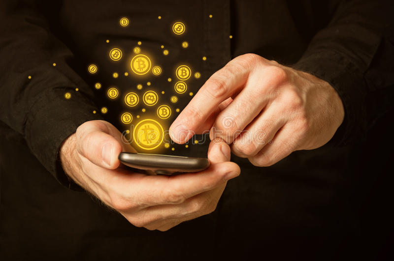 Bitcoins on smartphone royalty free stock photography