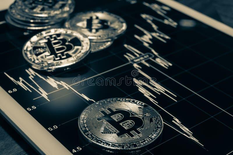 Bitcoins sur le comprimé montrant le graphique de représentation, noir et blanc photos stock
