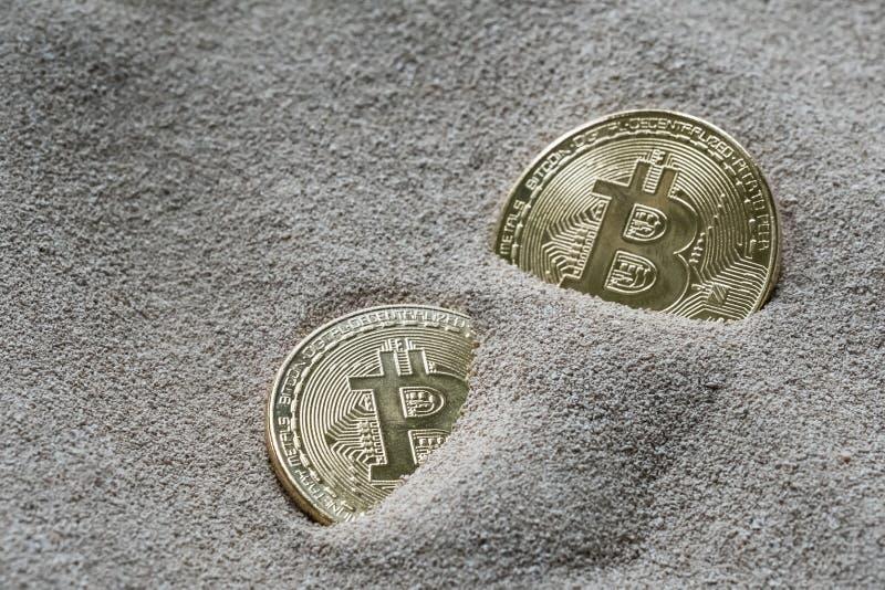 Bitcoins visto enterrado parcialmente en arena del silicio, en esta imagen del concepto de esta moneda crypto de la tecnología fotografía de archivo libre de regalías