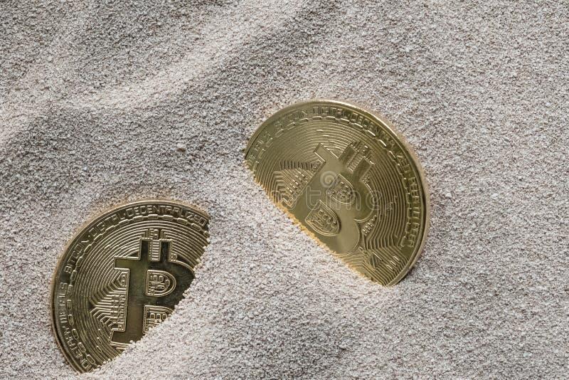 Bitcoins visto enterrado parcialmente en arena del silicio, en esta imagen del concepto de esta moneda crypto de la tecnología foto de archivo
