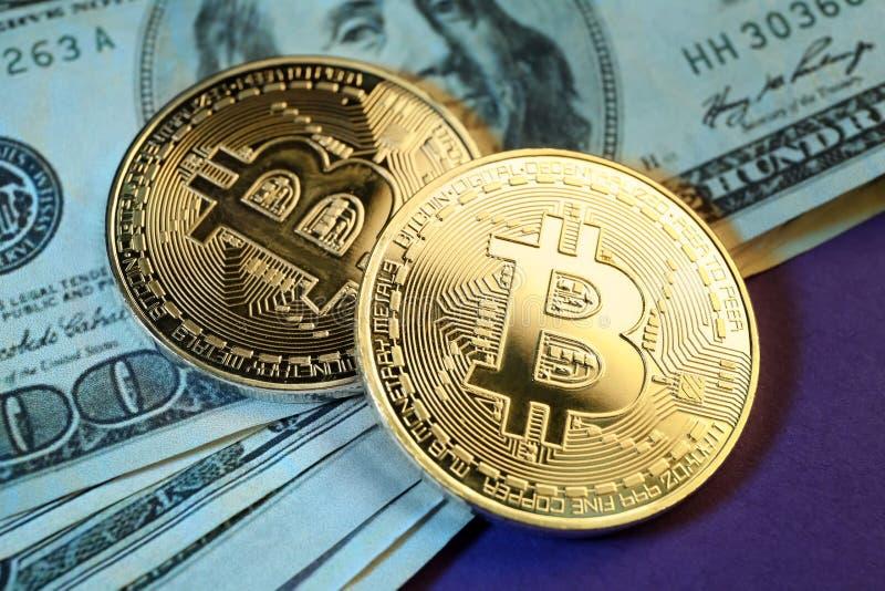 Bitcoins y billetes de banco del dólar en la tabla, primer imagenes de archivo