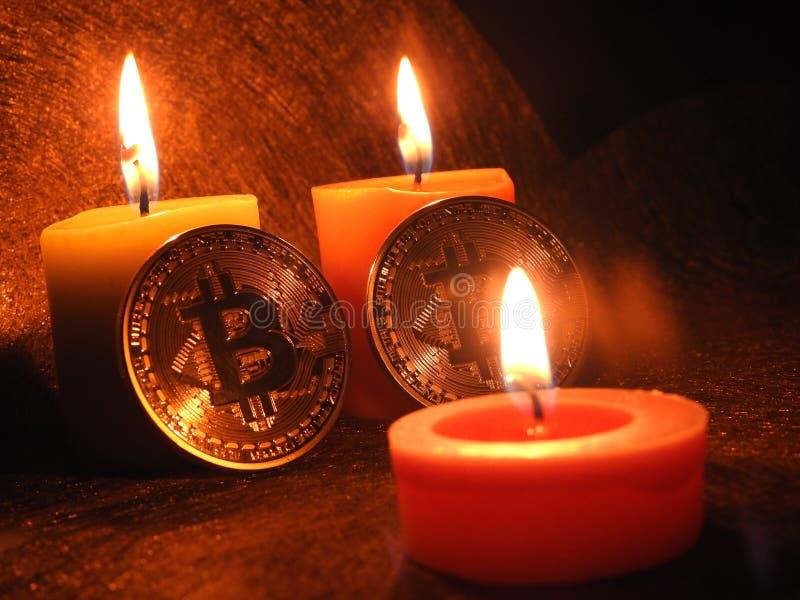 Bitcoins y luces de una vela imagenes de archivo