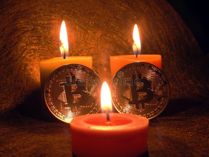 Bitcoins y luz de una vela imagenes de archivo