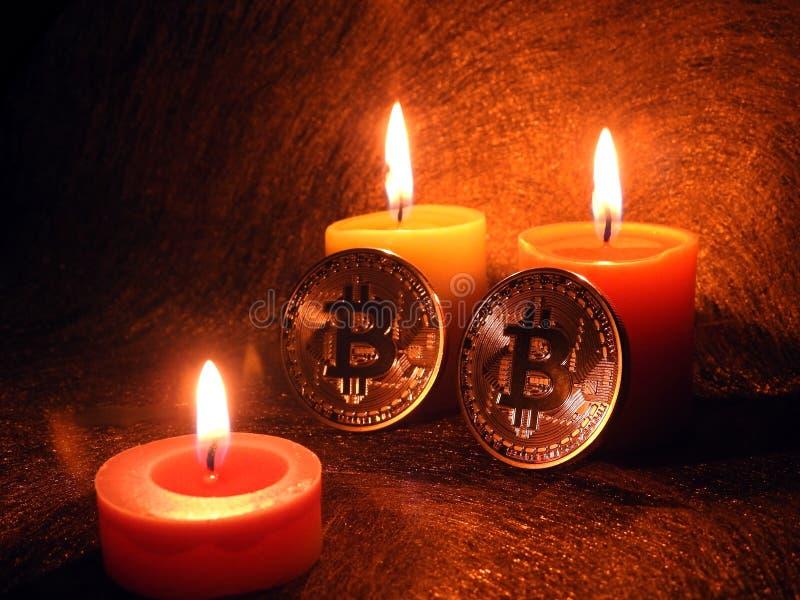 Bitcoins y ` s de la luz de una vela tres fotografía de archivo libre de regalías