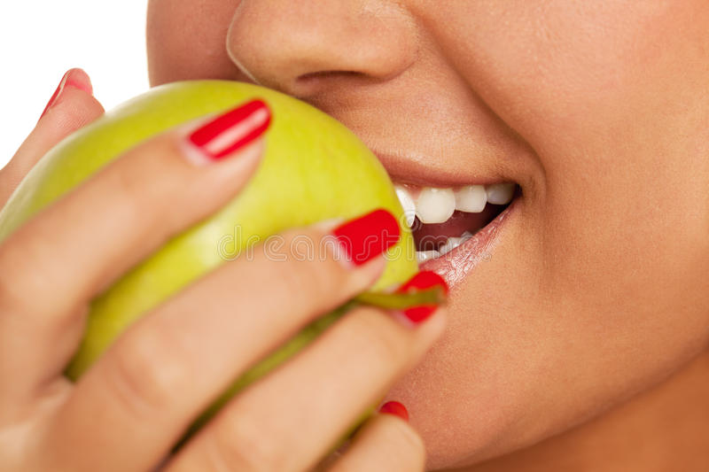 Bite the apple. Close-up of a person biting apple stock image
