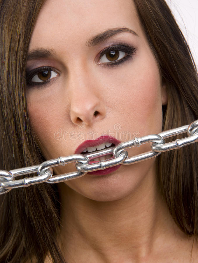 Download Beautiful Brunette Woman Appears To Bite The Chain Stock Image - Image: 25086187