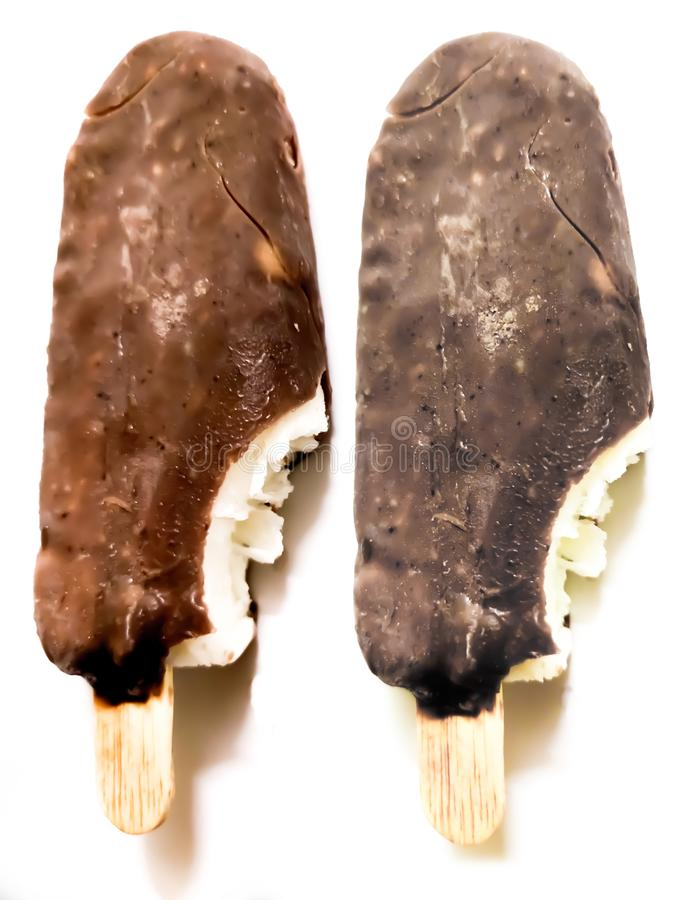 Bite ice cream covered by brown chocolate  on white background. Ice-cream, icecream, popsicle, closeup, food, lolly, stick, dessert, detail, sundae, fresh royalty free stock image