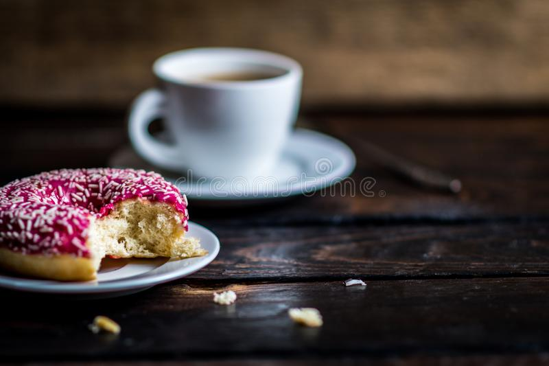 Bite a Pink donut with white sprinkle. And cup of coffee on wood table stock photo