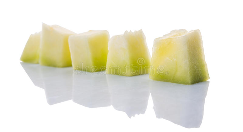 Bite Sized Honeydew Fruit I. Bite sized honeydew pieces over white background stock image