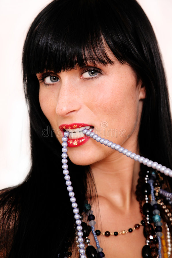 Bite success. Pearl biting woman living rich and full of luxury stock photos