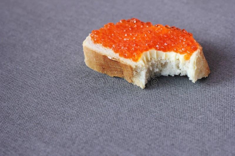 Biten av smörgås med den röda kaviaren på en grå bakgrund royaltyfria bilder