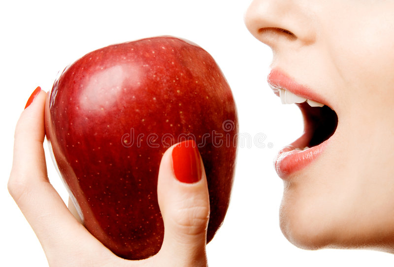 Biting apple. Closeup of a woman biting a red apple