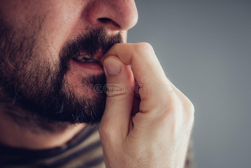 Biting fingernails. Close up of nervous male biting fingernails royalty free stock photography