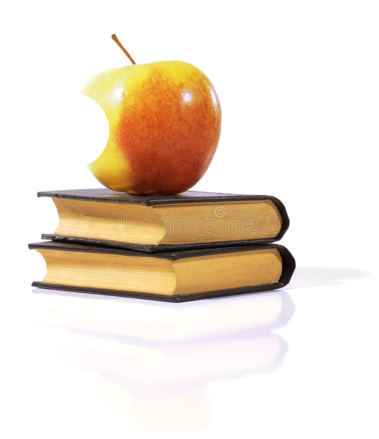 Bitten Apple on a books. royalty free stock image