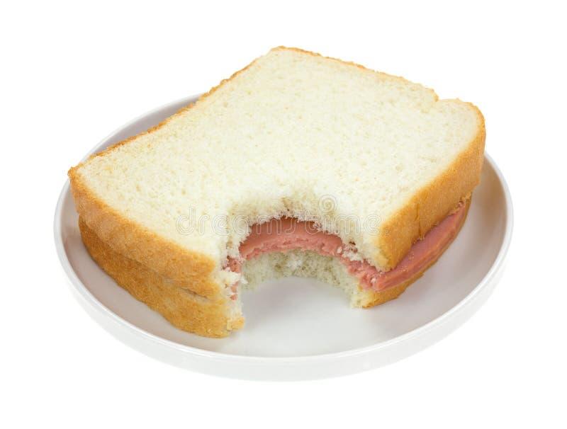 Bitten Baloney Sandwich On White Bread. A bitten baloney sandwich with white bread on a small plate
