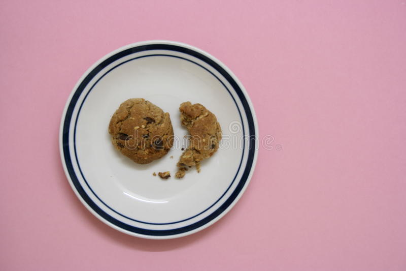 Bitten biscuit in a plate royalty free stock image