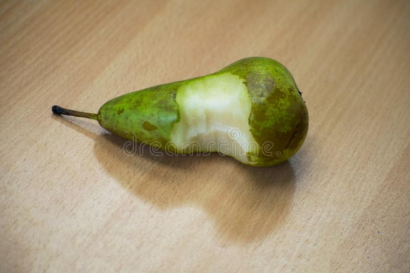 Bitten pear on a wooden table royalty free stock photos