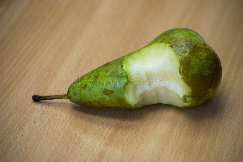 Bitten pear on a wooden table royalty free stock image