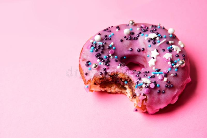 Bitten pink donut with a festive powder royalty free stock photography