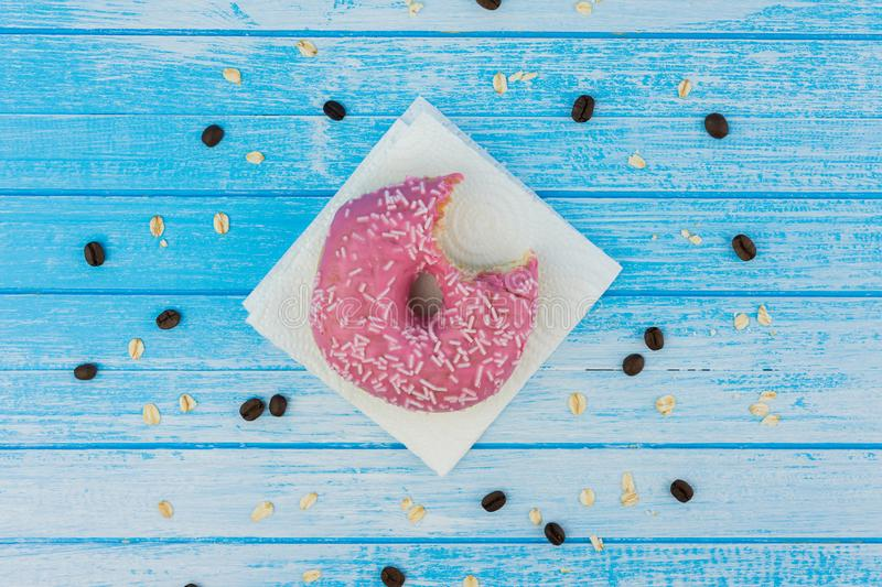 Bitten Tasty Sweet Donut On Paper On Scratched Blue White High C royalty free stock photography